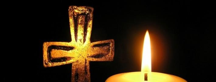 golden-cross-and-candle-in-dark-surroundings
